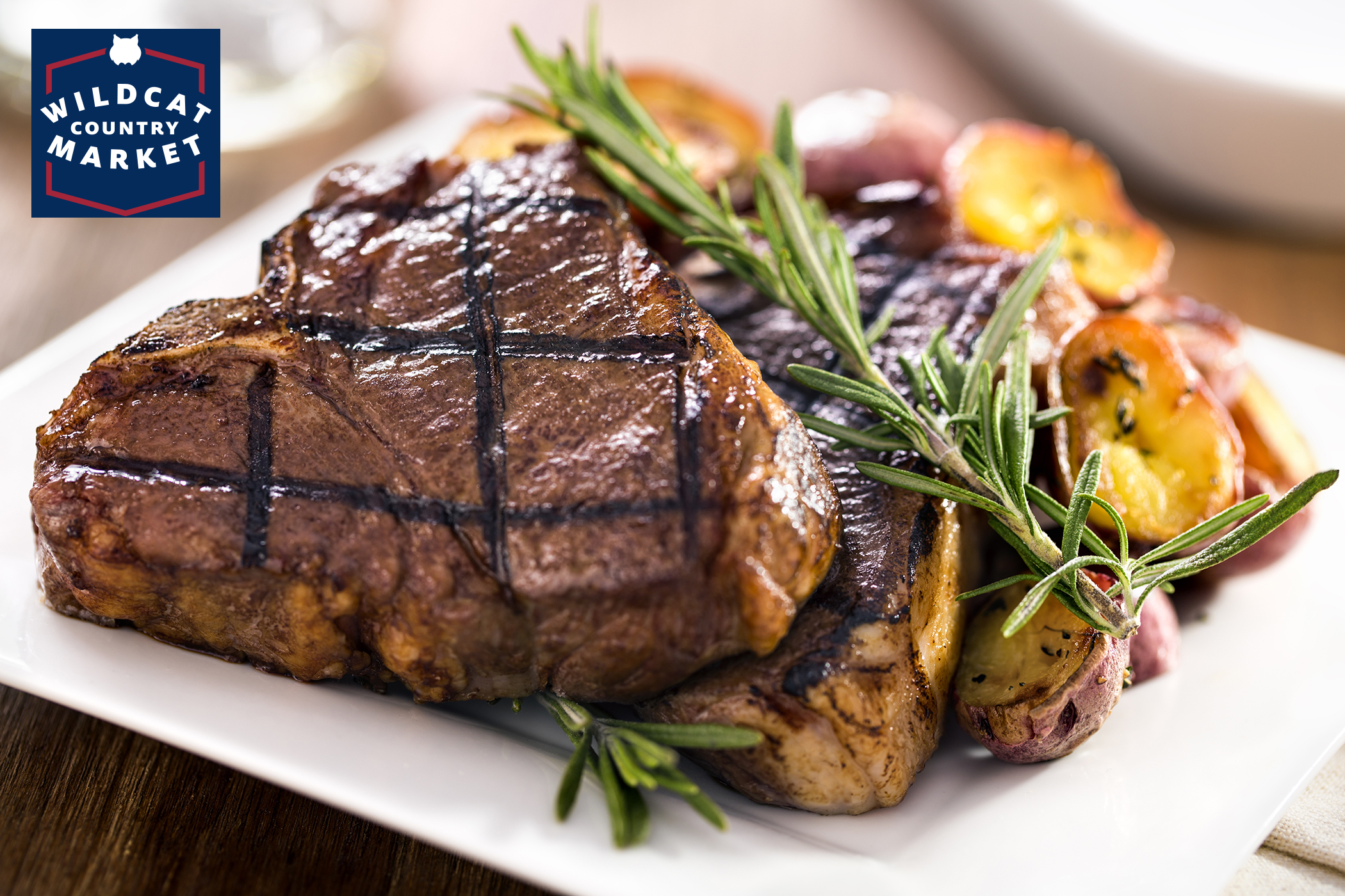 A meal of meat chops presented with fresh rosemary and roasted potatoes.